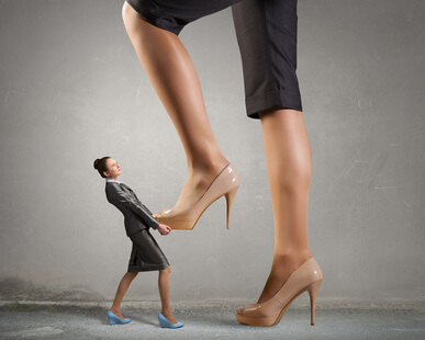 Businesswoman foot stepping on tiny businesswoman presenting power concept