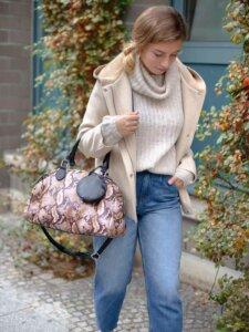 Junge Frau geht auf den Boden blickend einen Weg entlang, in ihrer Ellenbeuge eine große Handtasche