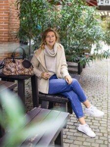 Junge Frau in sitzt lachend und mit überschlagenem Bein auf einer Bank