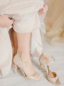 Fuß einer Frau, die sich einen cremefarbenen Absatzschuh anzieht