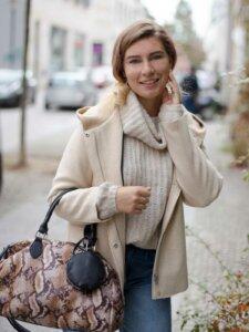 Junge Frau in cremefarbenem Strickpullover, beiger Jacke und große Henkeltasche mit Animalprint